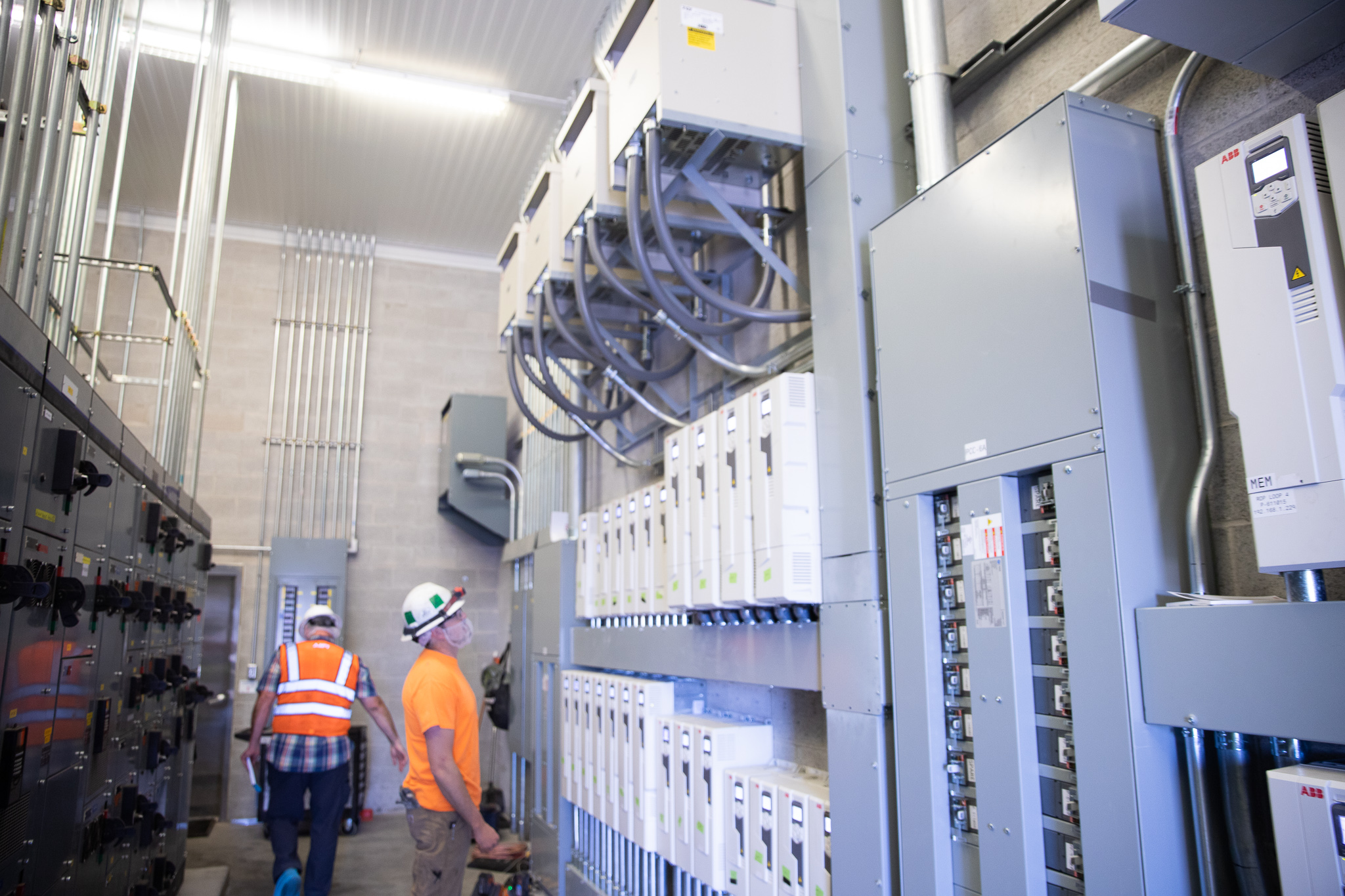 Image: 2 electricians examine industrial electrical boxes
